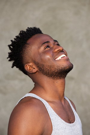 Side portrait of happy young black man looking up and smiling