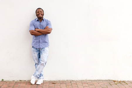 Full length portrait of cool young african man leaning against white wall and smiling Stok Fotoğraf