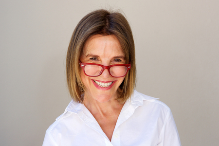 Close up portrait of smiling businesswoman with glasses against white wall