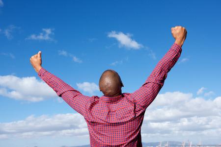 Portret van rug van zwarte man met opgeheven handen in de lucht