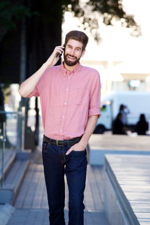 sidewalk talk: Portrait of cheerful man walking on sidewalk and talking on mobile phone