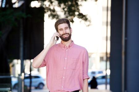 sidewalk talk: Portrait of cheerful man walking on sidewalk and talking on smart phone