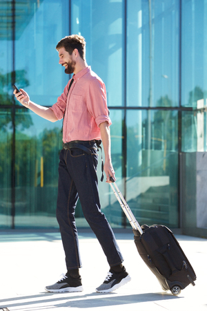 Side portrait of happy man walking with suitcase and cellphone in city
