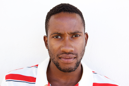 Close up portrait of young african american man looking serious against white background