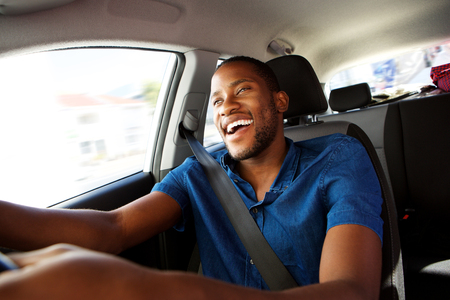 Portrait of happy young african man enjoying driving a car