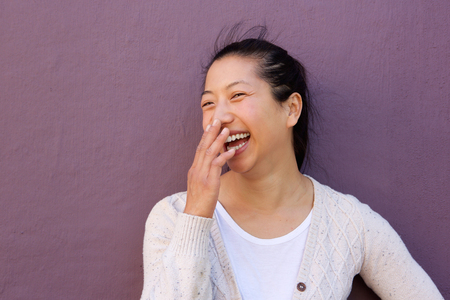 Close up portrait of cheerful asian woman laughing with hand on mouth against purple wall