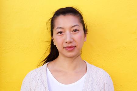 노란 벽에 아름다운 아시아 여자의 초상화를 닫습니다