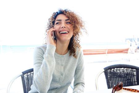 Portrait de jolie jeune femme assise à la table du café et parler au téléphone portable Banque d'images - 79894208