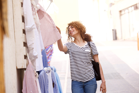 Portrait of happy young woman looking at clothes at store