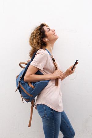 Zijportret van gelukkige jonge vrouw die aan muziek met mobiele telefoon en oortelefoons luisteren