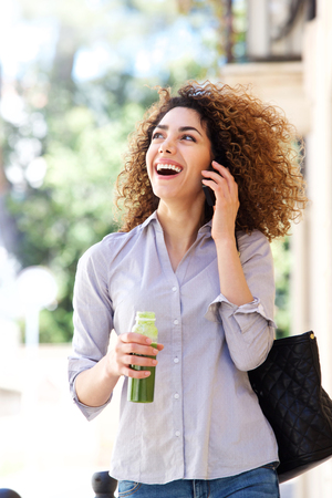 Portrait of happy young woman walking and talking on cell phone