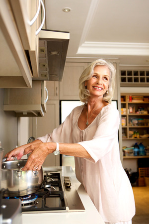 Portrait of smiling older woman putting pot on stove Imagens