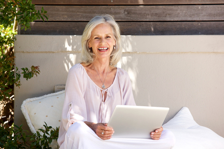 Portrait of older woman sitting and using laptop outside