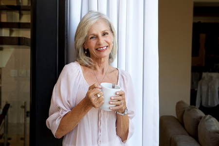 Portrait of smiling woman standing with cup of tea