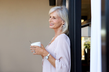Portrait of attractive older woman standing with cup of coffee