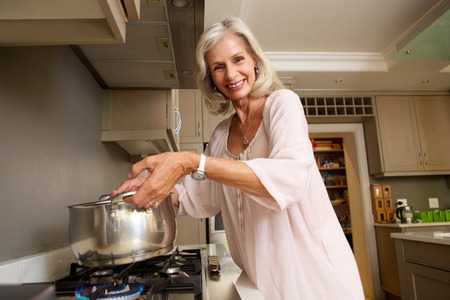 Portrait of smiling older lady lifting pot from stove Archivio Fotografico