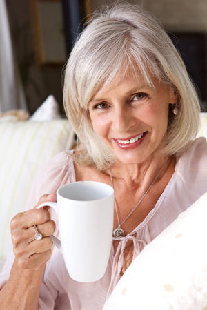 Portrait of older woman smiling with cup of coffee