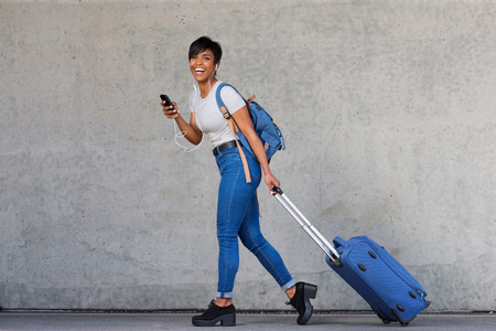 Full body portrait of young woman walking with travel bag and mobile phone Stock Photo