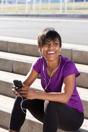 Portrait of fit young african woman relaxing with mobile phone and earphones, listening to music and relaxing after running workout session.
