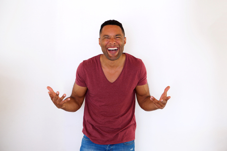 Portrait of overjoyed young african american man laughing on white background