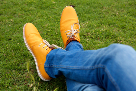 Close up portrait of man legs in jeans and shoes on green grass at park