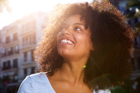 Close up side portrait of smiling african american woman outside in city