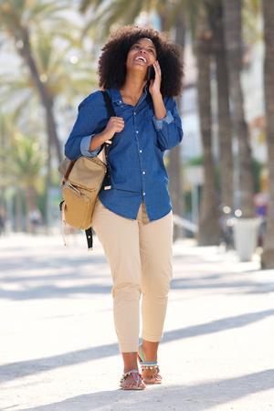 sidewalk talk: Full body portrait of smiling woman walking and talking outside on mobile phone