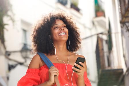 Sluit omhoog portret van gelukkige vrouw op straat met hoofdtelefoons en slimme telefoon