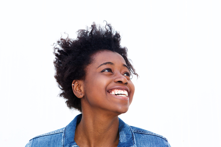 Close up portrait of young black woman looking away at copy space and smiling against white background