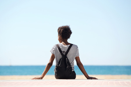 Rear view portrait of young woman sitting by the beach on summer day 스톡 콘텐츠