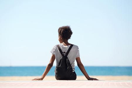 Porträt der hinteren Ansicht der jungen Frau sitzend durch den Strand am Sommertag Standard-Bild - 81319700