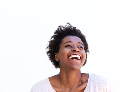 Close up portrait of cheerful young african american woman laughing against white background Stock Photo