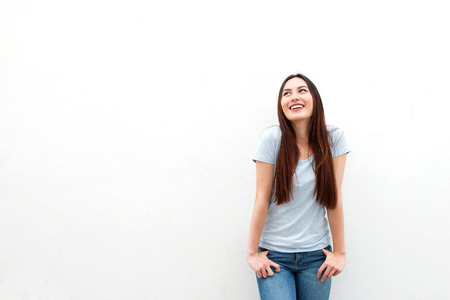 Portrait of cute young woman smiling and looking up on white background
