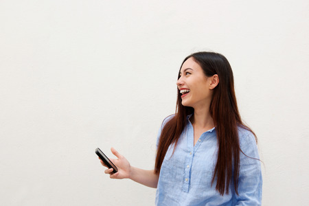 Close up side portrait of laughing woman with long hair holding mobile phone Standard-Bild