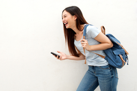 Portrait of laughing woman holding mobile phone and backpack
