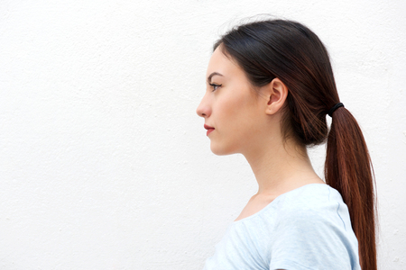 Close up side portrait of casual young woman standing alone