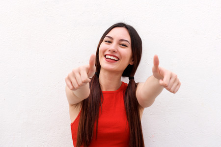 Close up portrait of positive young woman smiling with thumbs up Stock Photo