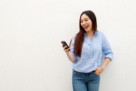 Portrait of beautiful woman holding mobile phone and laughing Foto de archivo