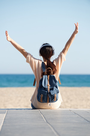 Rear portrait of woman with arms outstretched by sea with headphones