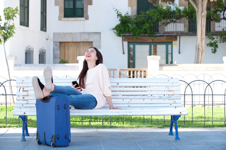Full body portrait of woman sitting with suitcase and phone on park bench 版權商用圖片