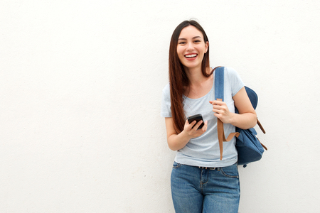Portrait of happy young woman standing with backpack and mobile phone