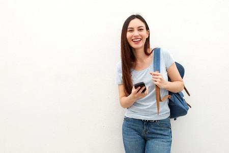 배낭과 휴대 전화로 서 행복 한 젊은 여자의 초상화 스톡 콘텐츠