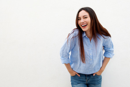 Portrait of laughing woman with long hair standing by white background Stock Photo