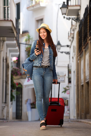 Full length portrait of woman walking on street with luggage holding mobile phone