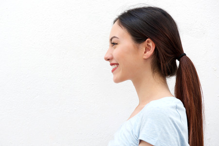 Close up side portrait of healthy young woman with long hair smiling 스톡 콘텐츠