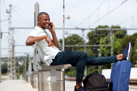 Portrait of afro american traveler sitting with luggage and talking on cellphone at train station 版權商用圖片