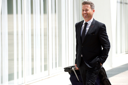 Portrait of smiling man on business trip walking with luggage Stock Photo