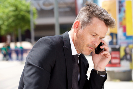 Close up side portrait of serious man in suit on business call outside