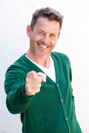 Close up portrait of smiling older man pointing finger on white background