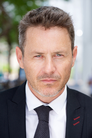 Close up portrait of serious businessman standing outside in suit and tie